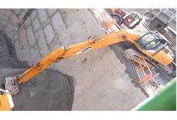 Длинорукий экскаватор на откопке котлована под фундамент